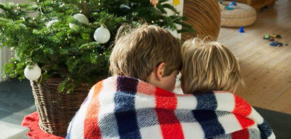 kaks last teki sees jõulupuu all istumas