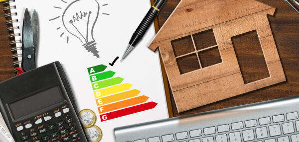 Energy efficiency rating graph on a desk with a wooden house model, calculator, folding ruler, light bulb and a computer keyboard