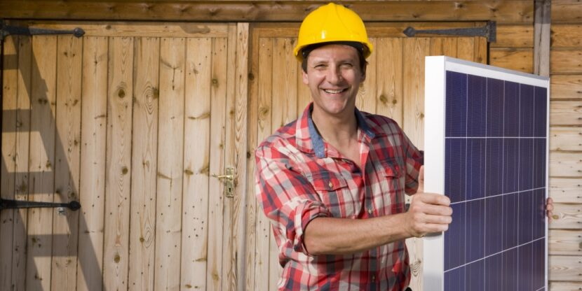 Portrait of smiling engineer holding solar panel in front of cabin