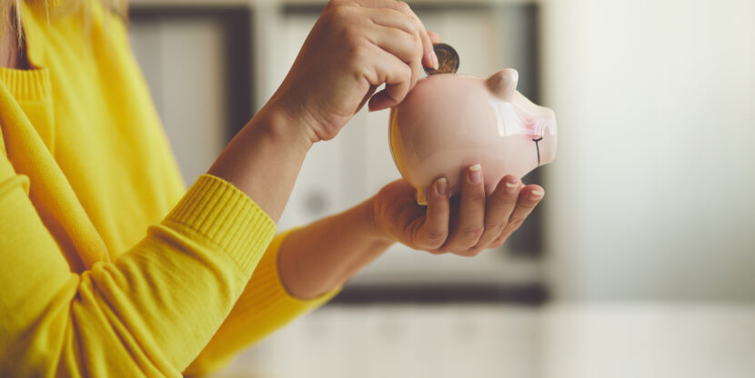 Woman inserts a coin into a piggy bank,