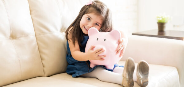 Portrait of beautiful little girl holding a big piggy bank in hands while sitting on sofa in living room
