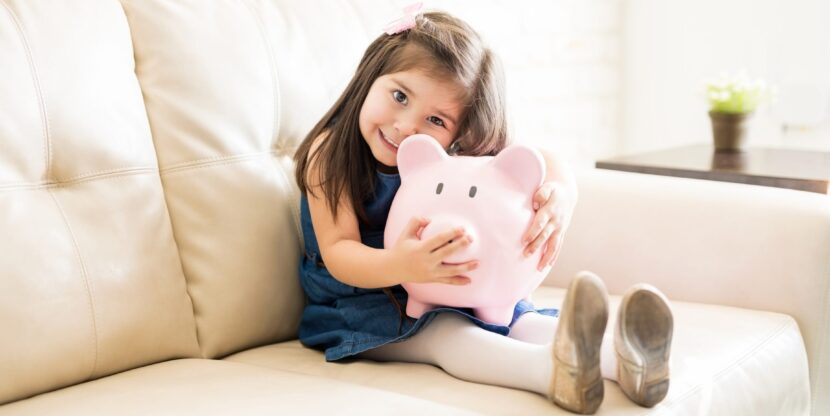 Portrait of little girl holding a big piggy bank in hands while sitting on sofa in living room