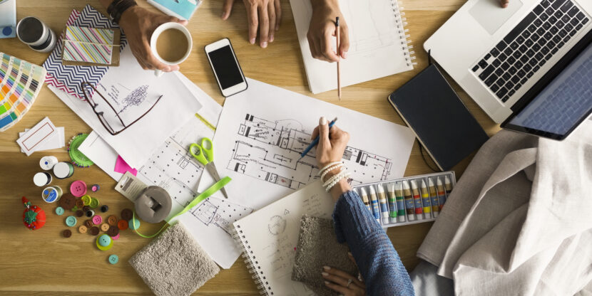 Ülalvaates arvutid, paberid ja erinevad kontoritarbed laua peal.
