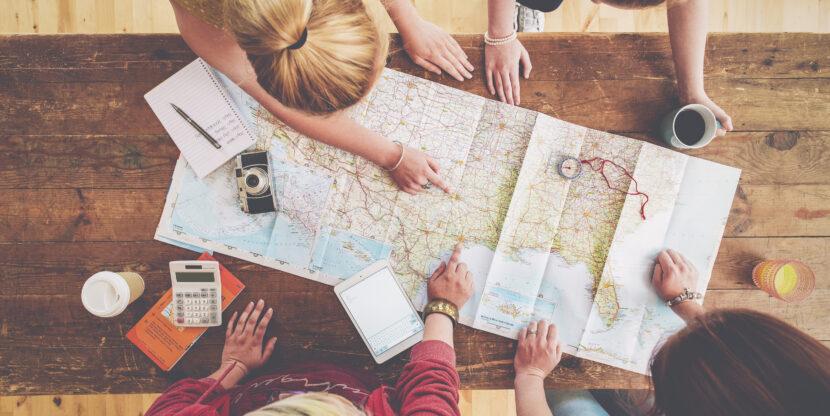 Kolm inimest kaarti vaatamas ja reisi planeerimas