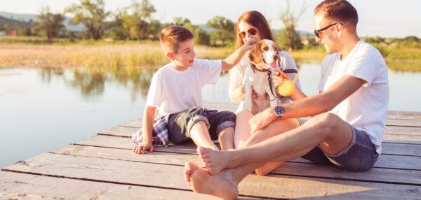 Kolmeliikmeline perekond: ema, isa ja poeg istuvad koos koeraga paadisillal ja mängivad. Suvine pilt